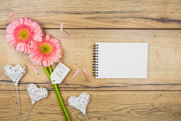 Blocco note vicino a fiori freschi con etichetta vicino a cuori ornamentali su bacchette