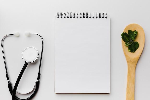 Blocco note vuoto circondato dallo stetoscopio e dal cucchiaio