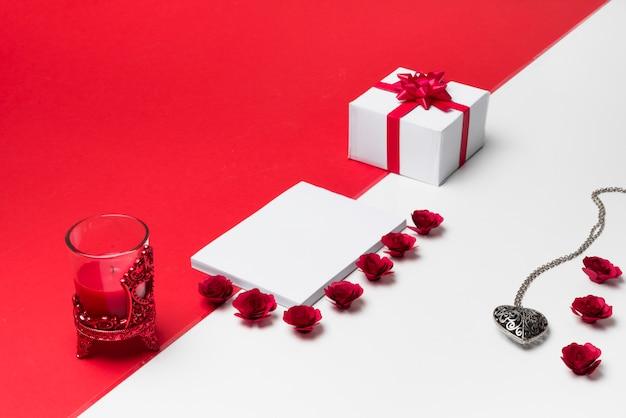 Blocco note vuoto con boccioli di rose sul tavolo