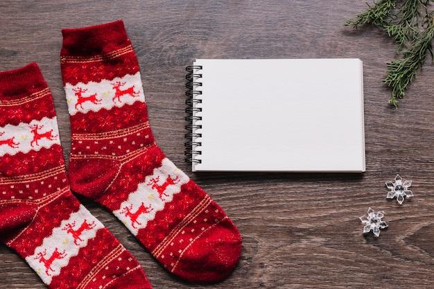 Blocco note vuoto con calze di natale sul tavolo