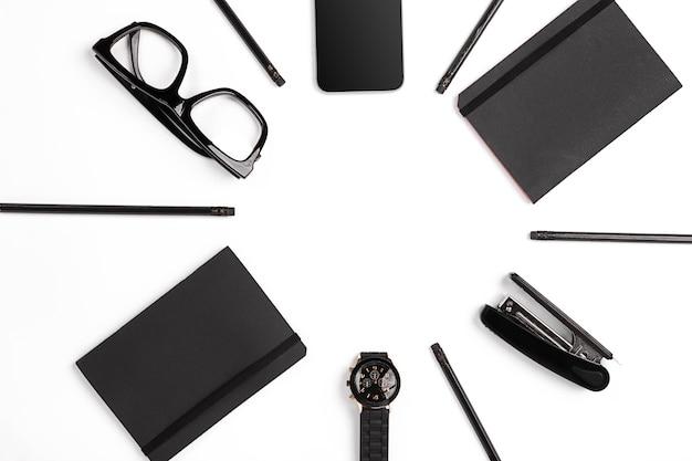 Blocco note vuoto con clip, penne e bicchieri piatti laici. vista dall'alto sul set di forniture per ufficio nero e occhiali su sfondo bianco