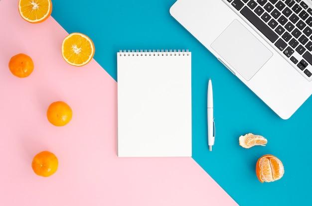 Blocco note vuoto con laptop e penna sulla superficie rosa e blu chiaro.