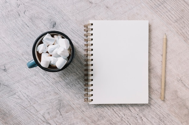 Blocco note vuoto con tazza di marshmallows