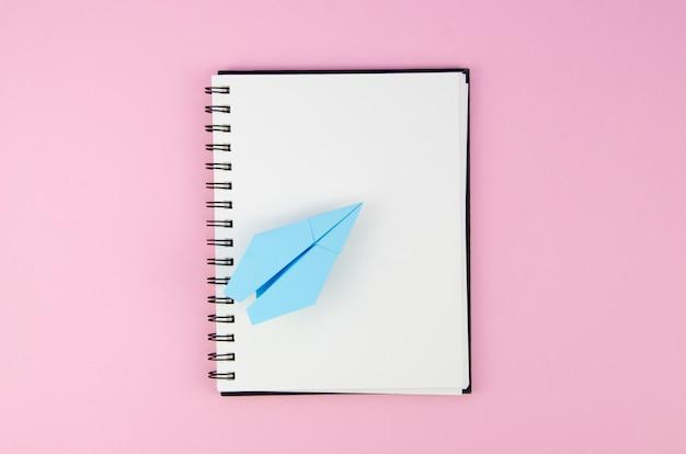 Blocco note vuoto dello spazio della copia con l'aereo di carta