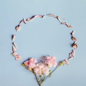 Blocco per grafici decorativo fatto con i fiori del garofano su priorità bassa blu
