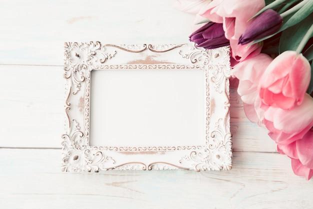 Blocco per grafici della foto e mazzo dei tulipani freschi su bianco