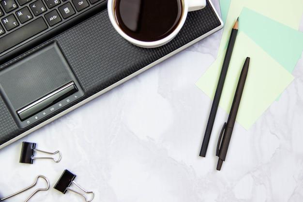 Blocco per grafici di affari con il computer portatile su una priorità bassa di marmo.