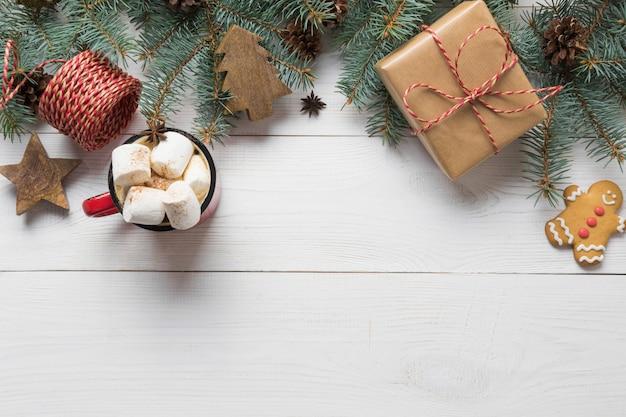 Blocco per grafici di natale dei rami dell'abete, dei giocattoli di legno e della tazza di caffè con la caramella gommosa e molle nel centro sul bordo di legno bianco. vista dall'alto.