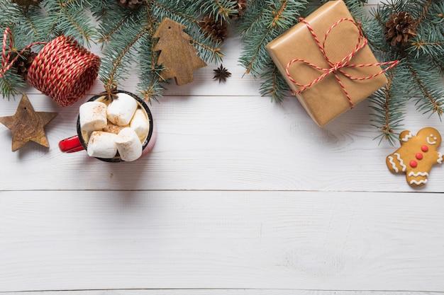 Blocco per grafici di natale dei rami dell'abete, dei giocattoli di legno e della tazza di caffè con la caramella gommosa e molle sul bordo di legno bianco