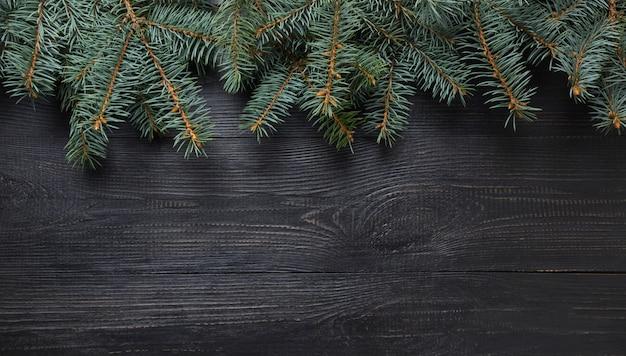 Blocco per grafici di natale di branche dell'abete sul bordo di legno scuro. vista dall'alto.