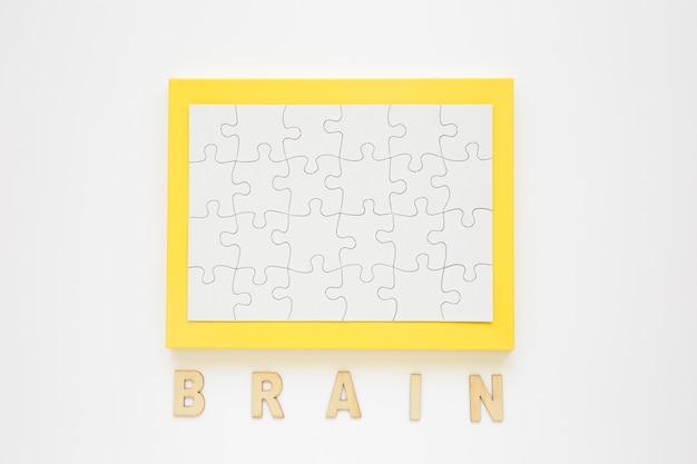 Blocco per grafici giallo con jigsaw puzzle vicino a parola del cervello