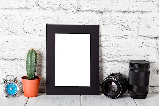 Blocco per grafici nero della foto del cartone sulla tabella bianca contro il muro di mattoni. mockup contro il muro di mattoni. modello