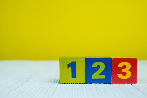Blocco quadrato numero 1 2 e 3 sul tavolo con il giallo