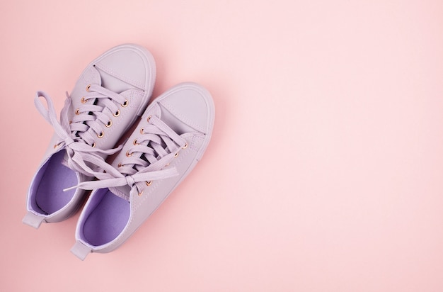 Blog di moda o concetto di rivista. scarpe da tennis femminili rosa su sfondo rosa pastello. immagine minima piatta vista dall'alto per lo shopping, le vendite, il blog di moda