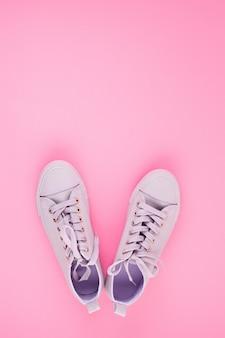 Blog di moda o concetto di rivista. scarpe da tennis femminili rosa su sfondo rosa pastello.