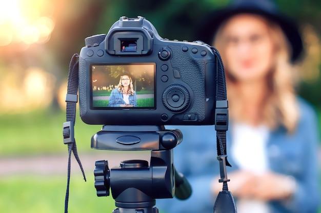 Blogger alla moda della ragazza che si siede sull'erba davanti alla macchina fotografica e sui tiri del video