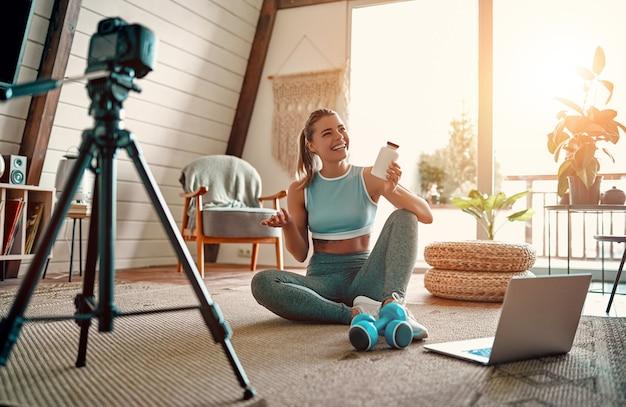 Blogger atletico della donna in abiti sportivi che si siedono sul pavimento con le teste di legno e un computer portatile e che mostrano un barattolo di nutrizione di sport alla macchina fotografica a casa nel salone. concetto di sport e tempo libero.