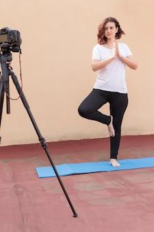 Blogger bruna che registra la routine di yoga