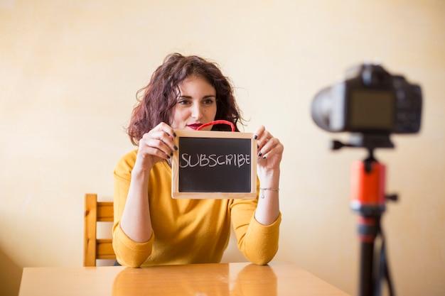 Blogger castana che mostra lavagna alla macchina fotografica