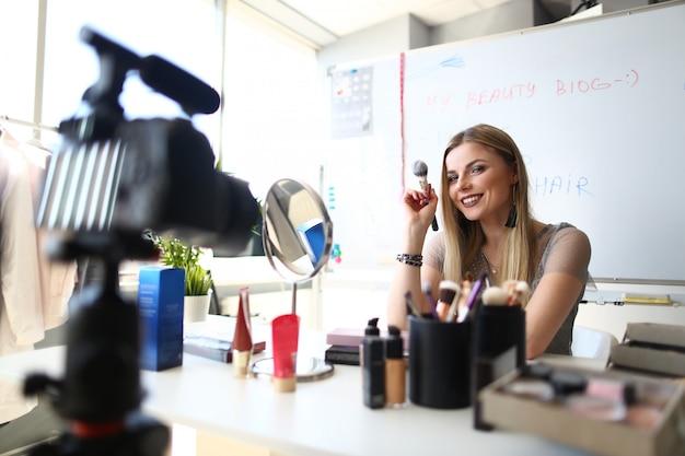 Blogger caucasico della donna che crea il blog del video di bellezza. i truccatori femminili che registrano i cosmetici applicano le punte.
