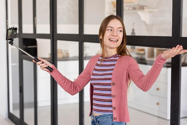Blogger che mostra la sua casa usando il selfie stick