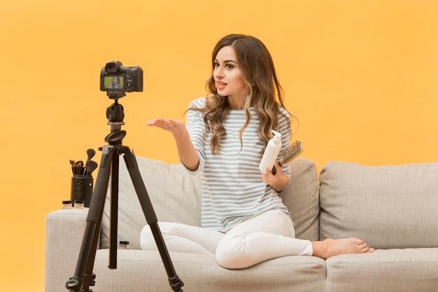 Blogger che presenta prodotti per capelli sulla fotocamera