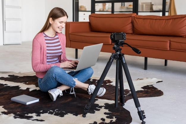 Blogger che utilizza il computer portatile e che si registra con la macchina fotografica