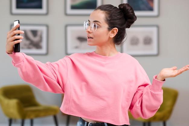 Blogger con gli occhiali che si registra con il telefono