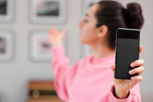 Blogger defocused che tiene il suo telefono
