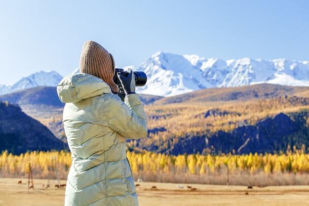 Blogger della donna che prende foto dalla macchina fotografica delle montagne del picco della neve.
