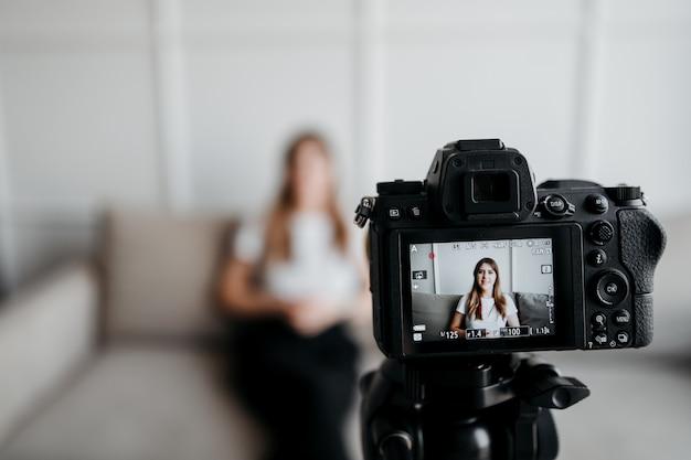 Blogger della donna della registrazione della macchina fotografica che parla con suoi seguaci che fanno vlog