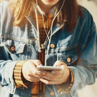 Blogger della giovane donna che passa in rassegna i social network sulla strada. donna che manda un sms sul suo telefono