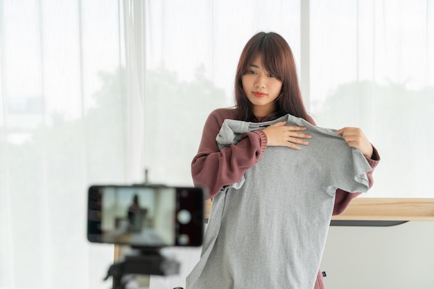 Blogger di bella donna asiatica che mostra i vestiti sulla macchina fotografica per la registrazione in diretta streaming video vlog nel suo negozio