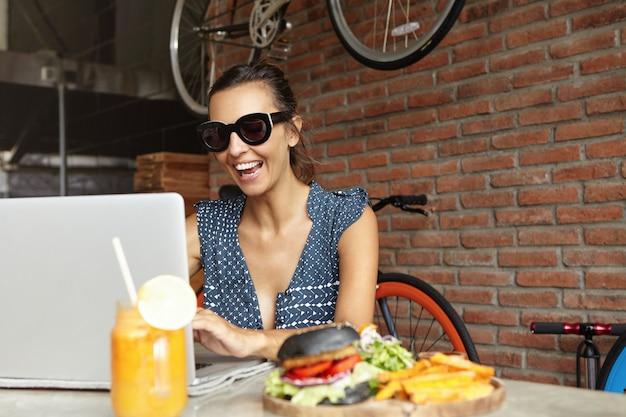 Blogger donna allegra in occhiali da sole alla moda che registra video webcam di se stessa per pubblicarla sul suo blog, utilizzando la connessione wireless a internet