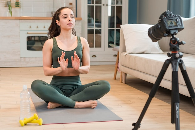 Blogger femminile in abiti sportivi che si siede sulla stuoia di yoga