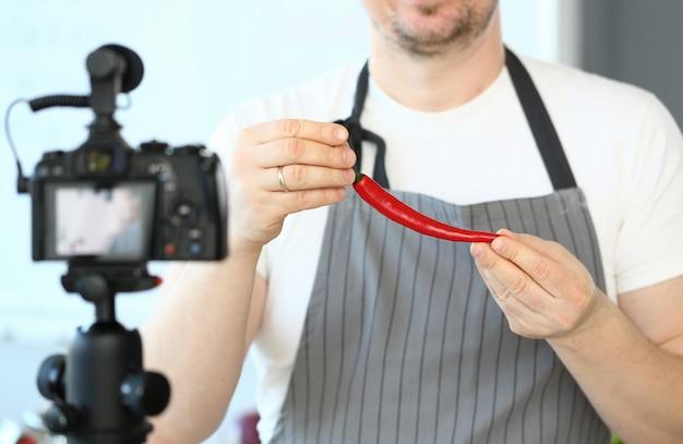 Blogger man recording red chili pepper recipe