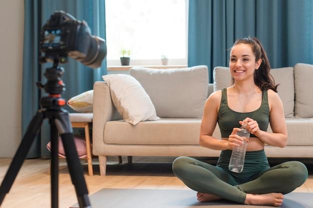 Blogger sportivo che si siede e che tiene bottiglia d'acqua