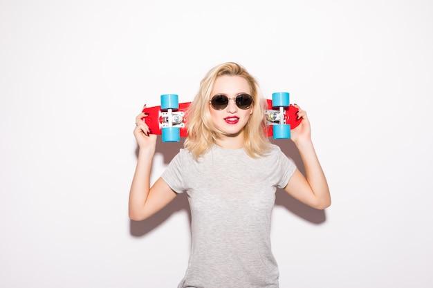 Blondie con skateboard rosso rimane davanti al muro bianco