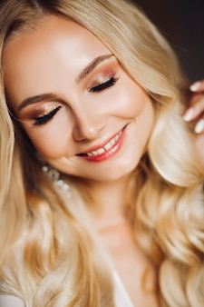Blondie giovane sensualità sorridente con gli occhi chiusi
