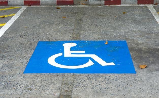 Blu handicap al parcheggio auto segno all'aperto per disabili.