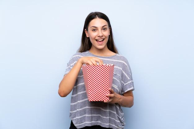 Blu isolato giovane donna castana che tiene una ciotola di popcorn