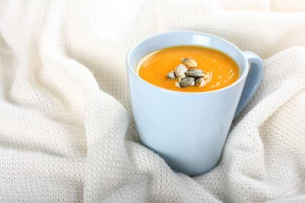 Blu tazza di zuppa di zucca sul tessuto di lana a maglia