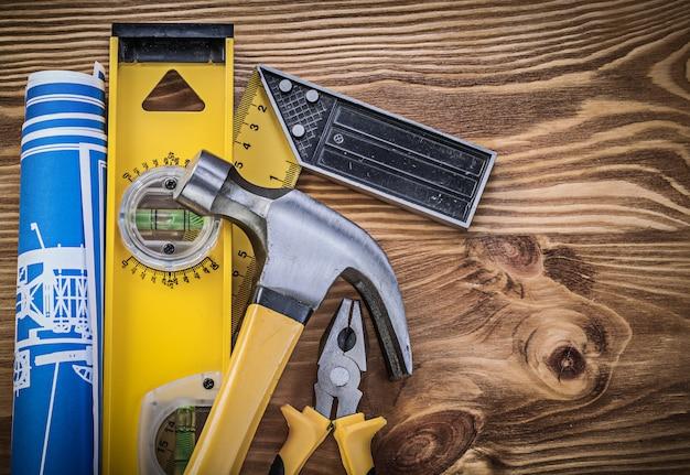 Blueprints costruzione livello righello quadrato martello da carpentiere pinze di presa su tavola di legno