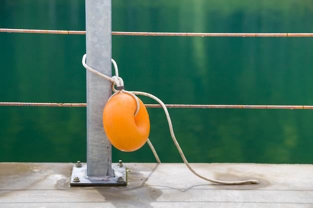 Boa di plastica gialla allegata a una recinzione metallica sulla riva di un lago con acqua verde.