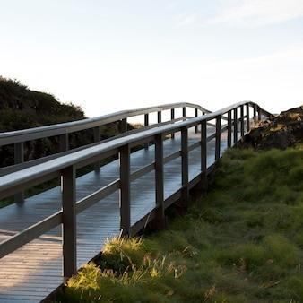 Boardwalk rotaia sopra collina erbosa