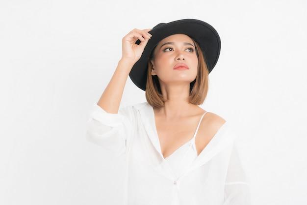 Bob corto marrone della donna asiatica del bello ritratto che porta cappello nero e camicia bianca nella posizione del basamento con la moda su fondo bianco isolato.