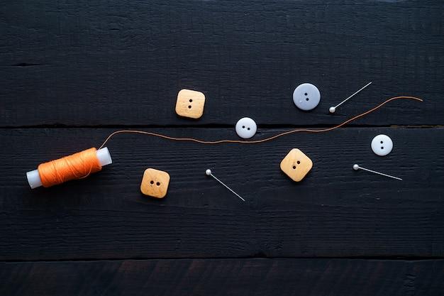 Bobina arancione di filo, spille e bottoni per cucire su una superficie nera in legno