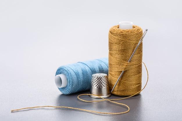 Bobina di fili blu e gialli. ditale e ago grande per il ricamo.