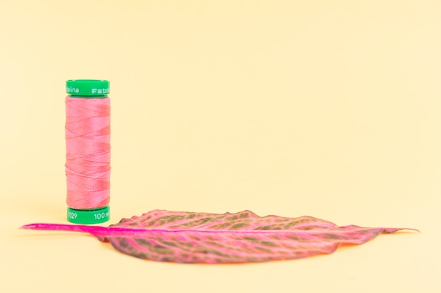 Bobina di filo rosa con una foglia