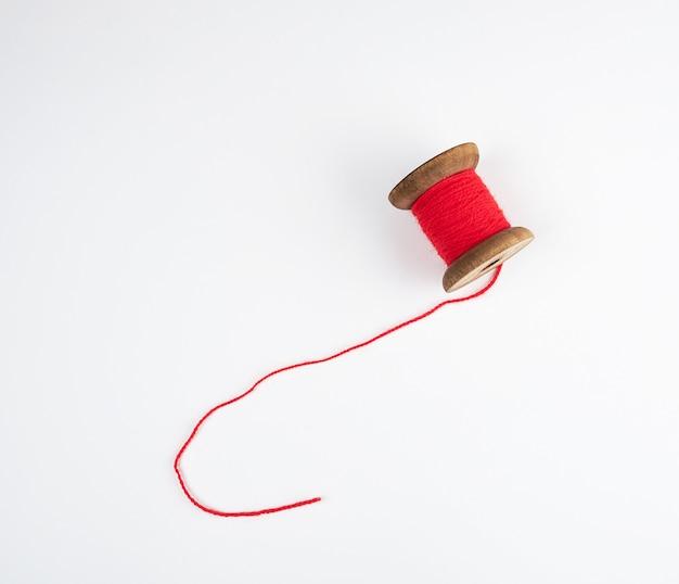 Bobina di legno con fili di lana rossa su bianco